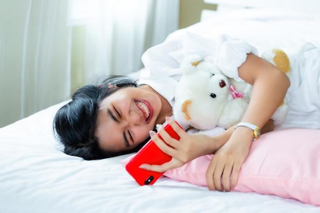Linda mujer adolescente alegre con teléfono inteligente en la cama