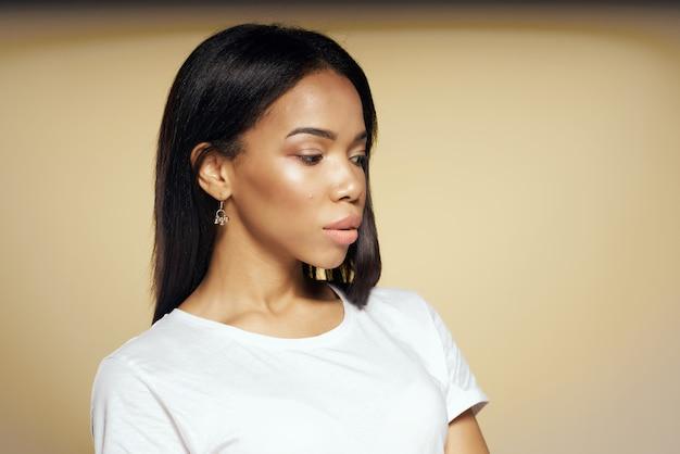 Linda mujer africana en camiseta blanca pelo largo posando de cerca