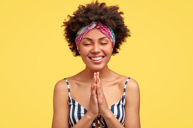 Linda mujer afroamericana feliz mantiene las manos en gesto de oración, tiene una amplia sonrisa, ora antes de un evento importante, vestida con una camiseta a rayas, posa contra la pared amarilla. cree en lo mejor