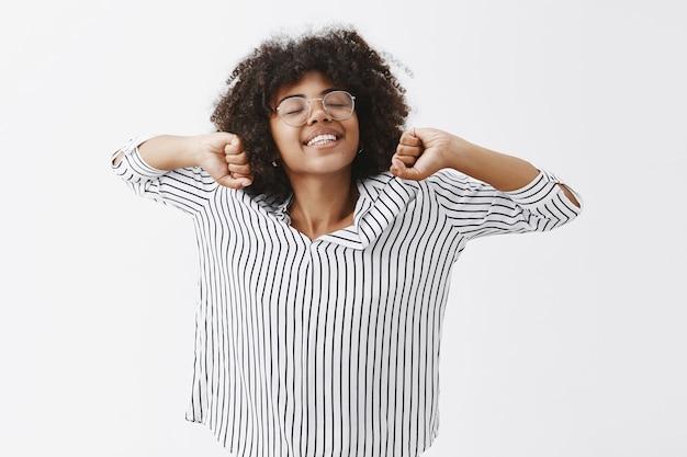 Linda mujer afroamericana que durmió bien estirando las manos y sonriendo felizmente después de una gran siesta lista para trabajar productivamente después de un buen descanso