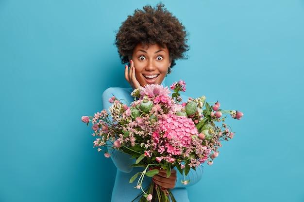 Linda mujer alegre toca la cara suavemente sostiene un gran ramo de flores