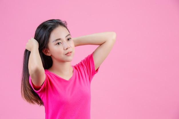 Linda mujer asiática blanca se posa con un cabello rosado en un rosa.