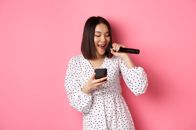 Linda mujer asiática leyendo letras en smartphone, cantando con micrófono, de pie en vestido de moda sobre rosa.
