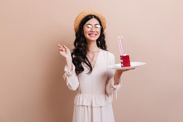 Linda mujer asiática riendo mientras hace deseo de cumpleaños. refinada mujer japonesa con sombrero sosteniendo un pedazo de pastel.