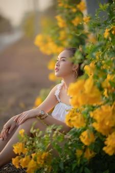Linda mujer asiática sentarse cerca de la flor y mirando el cielo sobre el fondo del atardecer