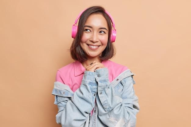 Linda mujer asiática soñadora mantiene las manos juntas piensa en algo agradable disfruta de la mejor aplicación de música en un dispositivo moderno, buena calidad de sonido, usa una camiseta casual, chaqueta vaquera aislada en una pared beige