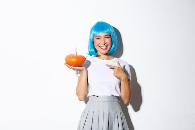 Linda mujer asiática sonriente con peluca azul apuntando con el dedo a la pequeña calabaza, celebrando halloween, de pie.