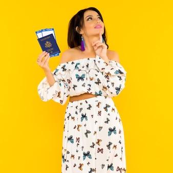 Una linda mujer asiática con un vestido de seda con mariposas sostiene un pasaporte y boletos de avión