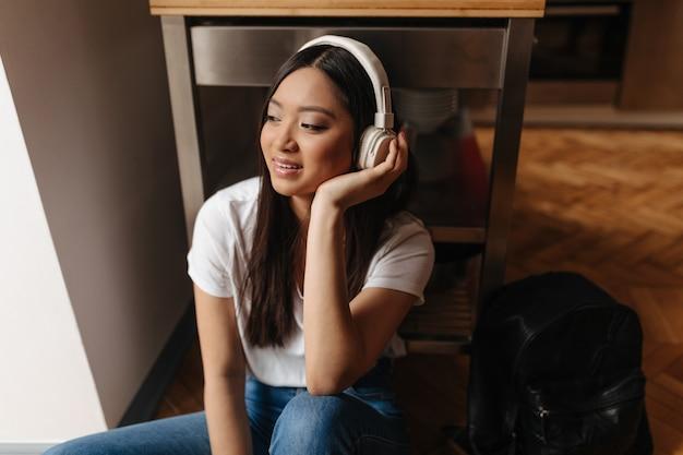 Linda mujer en auriculares descansando y sentada en el suelo en auriculares