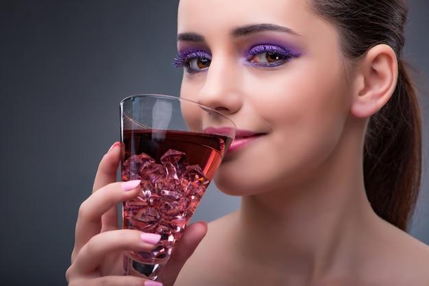 Linda mujer bebiendo cóctel rojo