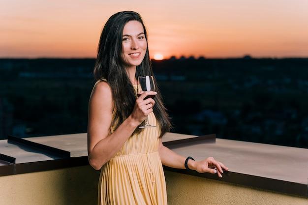 Linda mujer bebiendo vino en la azotea al amanecer