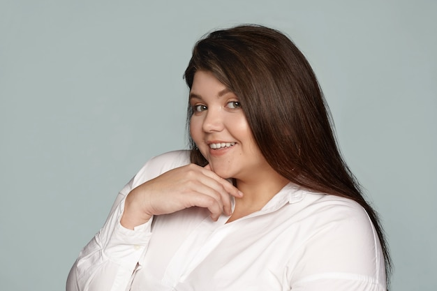 Linda mujer bonita con mejillas regordetas y cabello largo oscuro posando en camisa blanca coqueteando contigo, mirando y sonriendo ampliamente, con expresión facial misteriosa y juguetona coqueta