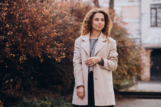 Linda mujer con cabello rizado caminando en un abrigo de otoño