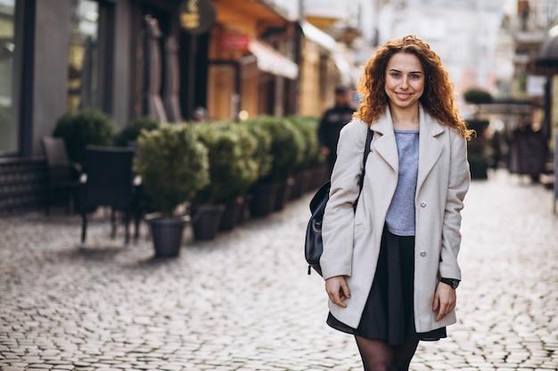 Linda mujer con cabello rizado caminando en una calle de café