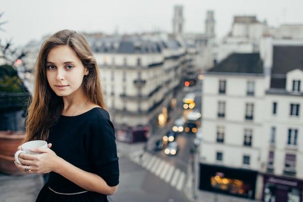 Linda mujer con café en el balcón