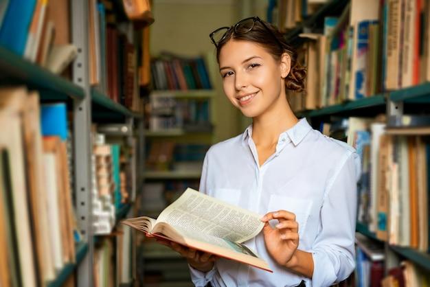 Una linda mujer con una camisa blanca en la biblioteca está sonriendo