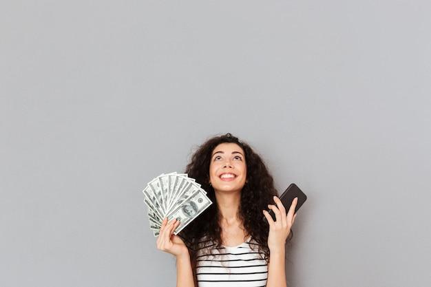 Linda mujer en camiseta a rayas con abanico de billetes de 100 dólares y un teléfono celular en las manos mirando agradecida no puede creer en su triunfo