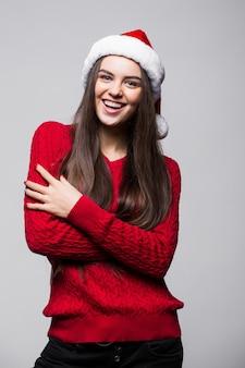 Linda mujer caucásica joven con gorro de papá noel y guantes posando sonriendo contra la pared gris claro. concepto de navidad y año nuevo. copie el espacio disponible.