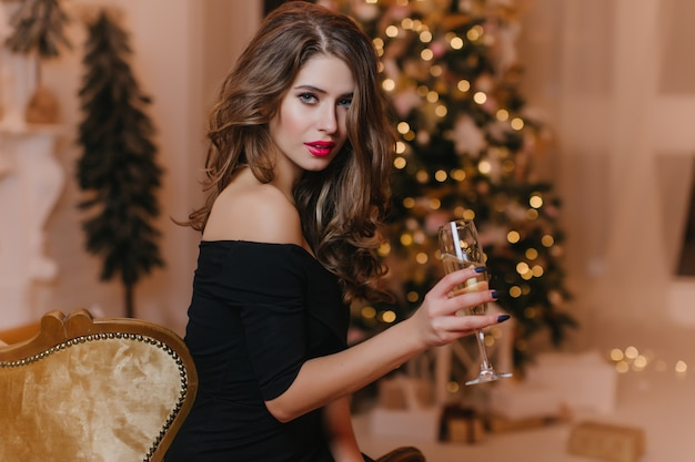 Linda mujer caucásica con pelo rizado sentado en el sofá y bebiendo champán en año nuevo. retrato de interior de niña confiada en ropa negra posando con vino cerca del árbol de navidad.