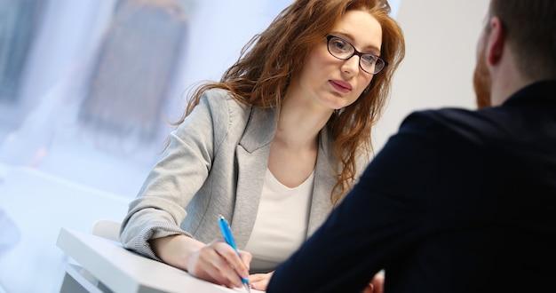 Linda mujer cuestionando al solicitante de empleo durante la entrevista