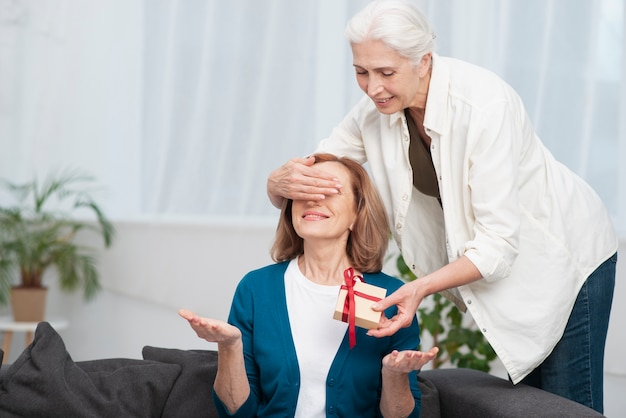 Linda mujer dando un regalo a su amiga