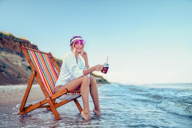 Linda mujer descansando en una tumbona playa y bebe agua de soda