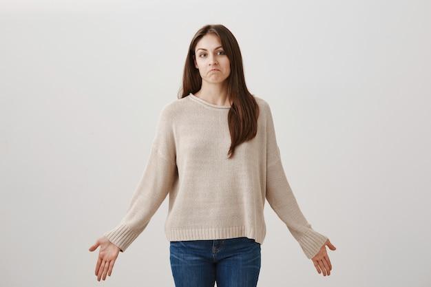 Linda mujer despistada encogiéndose de hombros y extendiendo las manos hacia los lados, sin darse cuenta, no sabe nada