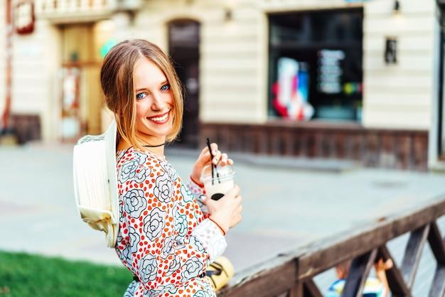 Linda mujer disfrutando de una bebida fría al aire libre en la calle