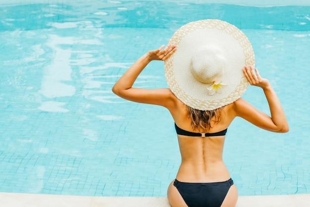 Linda mujer disfrutando de una piscina en el resort