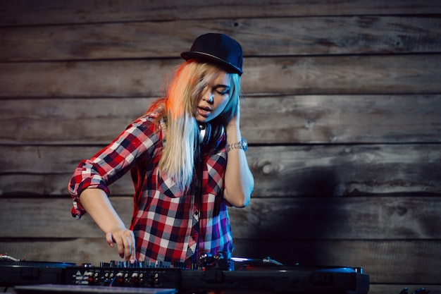 Linda mujer dj divirtiéndose tocando música en la fiesta del club