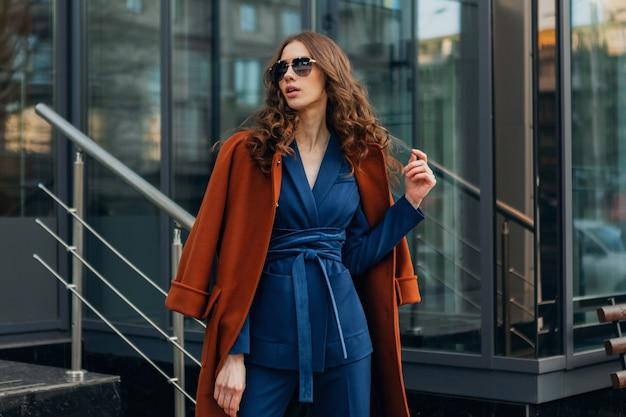 Linda mujer elegante con caminar en la calle de negocios de la ciudad urbana vestida con abrigo marrón cálido y traje azul, estilo callejero de moda primavera otoño, con gafas de sol