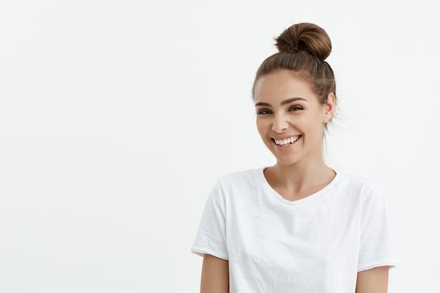 Linda mujer europea de moda con bollo sonriendo ampliamente y mirando a la cámara mientras está de pie sobre un espacio en blanco