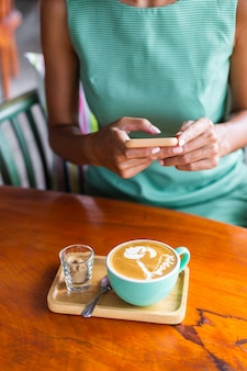 Linda mujer feliz tranquila elegante en vestido verde de verano se sienta con café en la cafetería disfrutando de la mañana