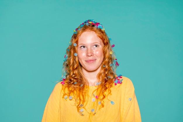 Linda mujer de fiesta con confeti en el pelo