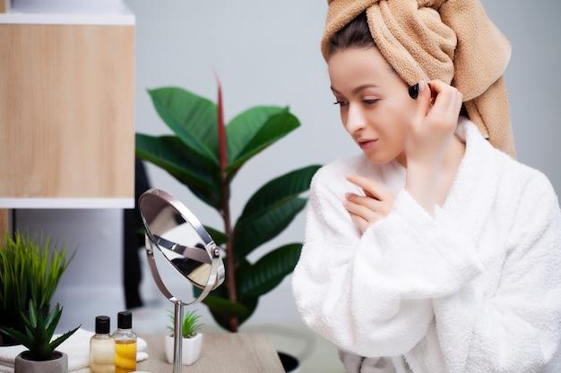 Linda mujer haciendo procedimientos cosméticos en casa frente al espejo
