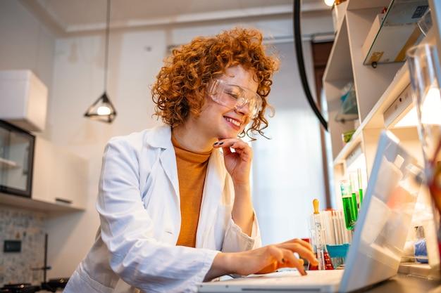 Linda mujer investigadora médica / científica que comprueba los resultados en su cuaderno mientras usa el microscopio electrónico en un laboratorio.