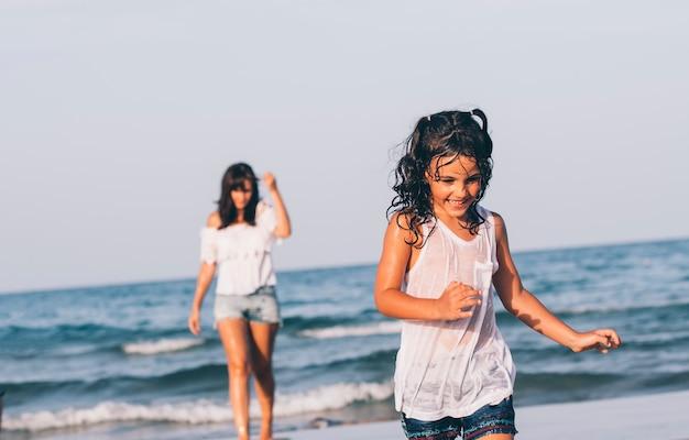Linda mujer con jeans cortos y su hija jugando en el agua de la playa