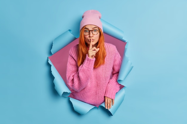 Linda mujer de jengibre silenciosa hace un gesto secreto presiona el dedo índice a los labios y pide no difundir rumores vestida con un suéter de punto informal y un sombrero.