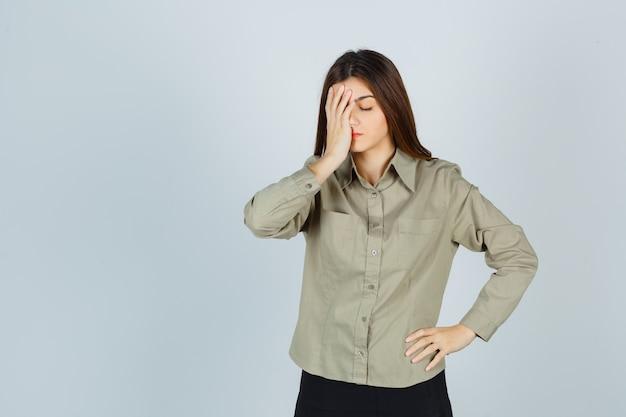 Linda mujer joven en camisa, falda sosteniendo la mano en la cara y mirando angustiado, vista frontal.