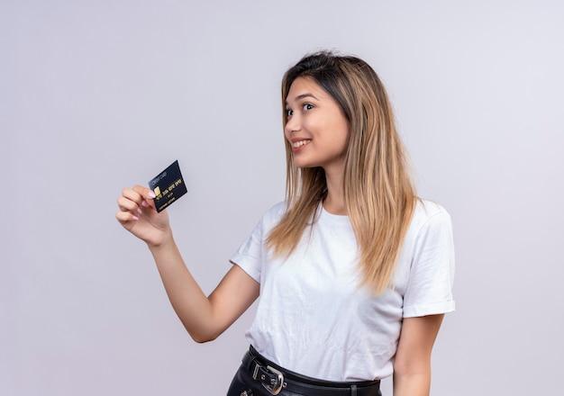 Una linda mujer joven en camiseta blanca sonriendo y mostrando la tarjeta de crédito en una pared blanca