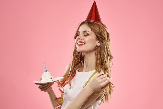 Linda mujer joven con un cupcake y velas celebra cumpleaños, estudio, fondo rosa