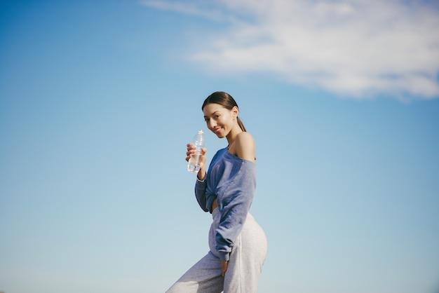 Linda mujer joven entrenando con una botella de agua
