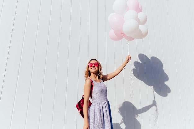 Linda mujer joven en gafas de sol de color rosa disfrutando del día soleado, sosteniendo globos de aire