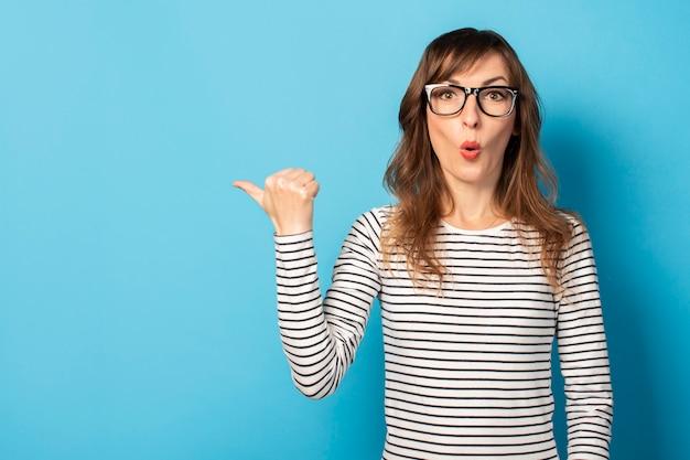 Linda mujer joven con gafas y un suéter de rayas apunta con su pulgar hacia el lado, una cara sorprendida, en azul. cara emocional