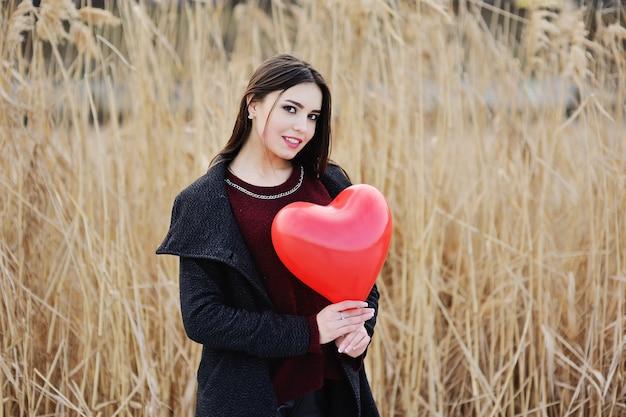 Linda mujer joven con un globo rojo en un campo