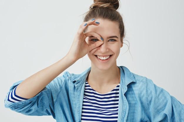 Linda mujer joven haciendo gesto de monóculo y mirando a través de los dedos