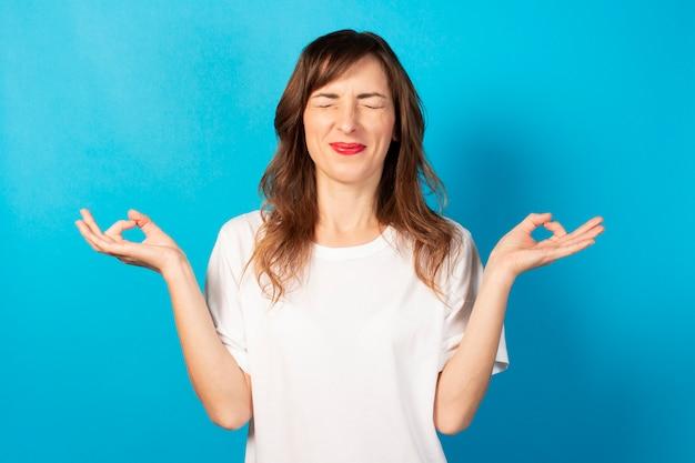 Linda mujer joven con los ojos cerrados y una camiseta blanca hace un gesto con sus manos yoga, concentración, meditación en azul aislado. concepto de meditación, sueños, planificación, buen humor.