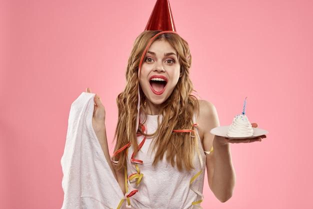 Linda mujer joven con un pastelito y velas celebra cumpleaños, estudio, espacio rosa