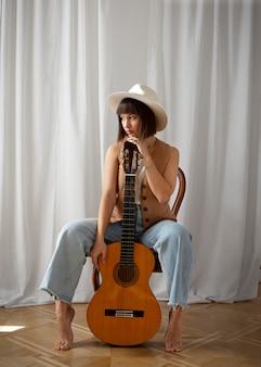 Linda mujer joven posando con una guitarra en el interior