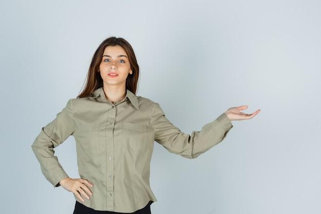 Linda mujer joven que muestra un gesto de bienvenida en camisa y una mirada apacible. vista frontal.